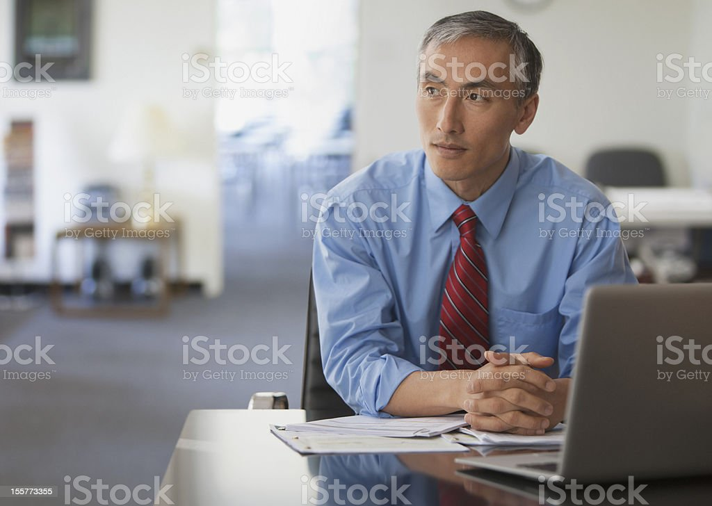 Pensive businessman with hands folded royalty-free stock photo