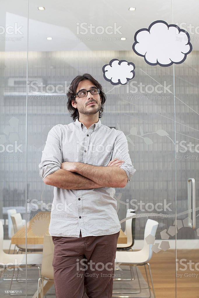 Pensive businessman with thought bubbles overhead royalty-free stock photo