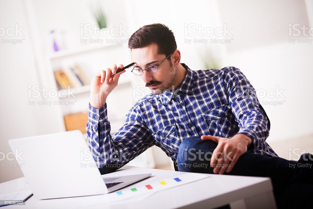 Pensive businessman working in home office using laptop. stock photo