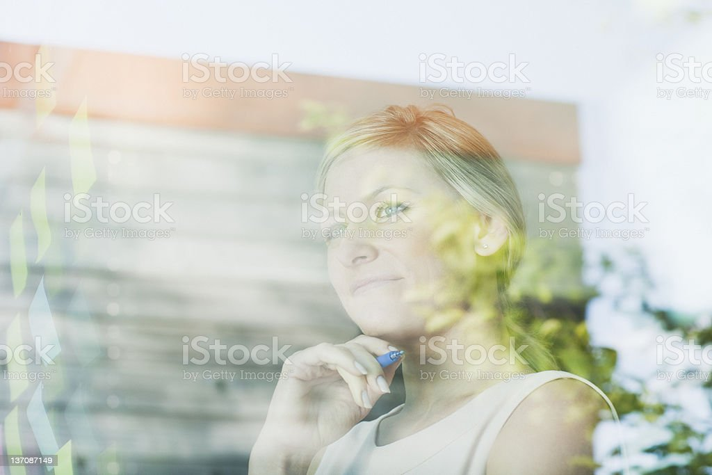 Pensive businesswoman at office window with adhesive notes royalty-free stock photo