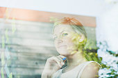 Pensive businesswoman at office window with adhesive notes