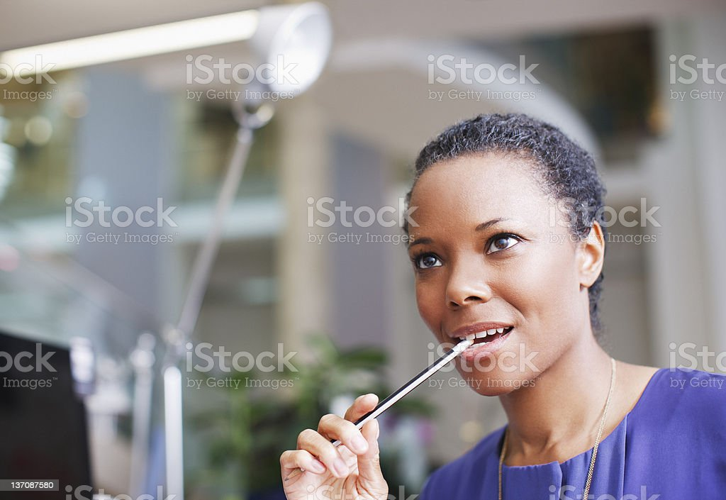 Pensive businesswoman biting end of pencil in office royalty-free stock photo