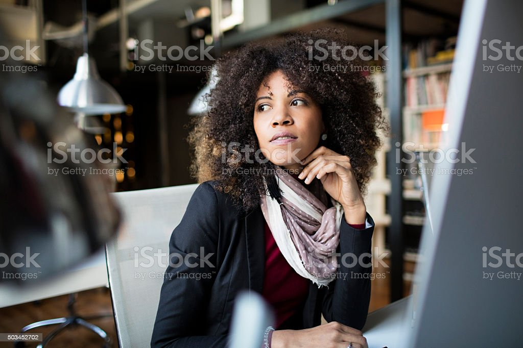 Pensive businesswoman looking away in office stock photo