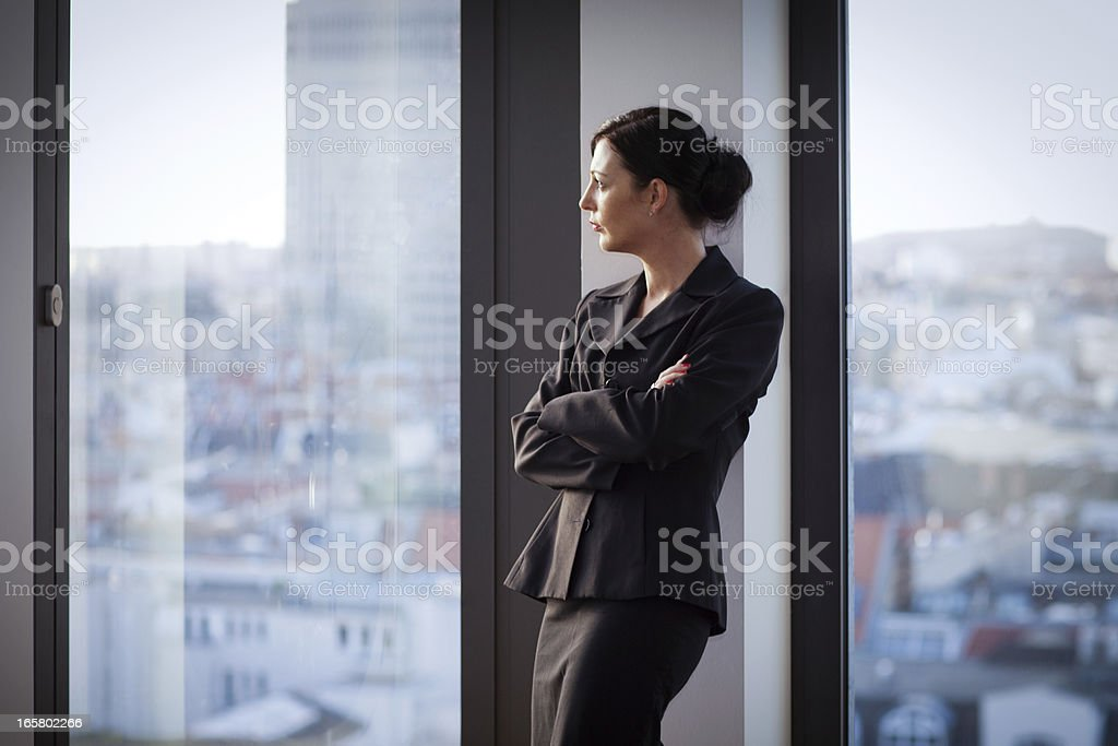 pensive Businesswoman looks out of the window to the skyline royalty-free stock photo