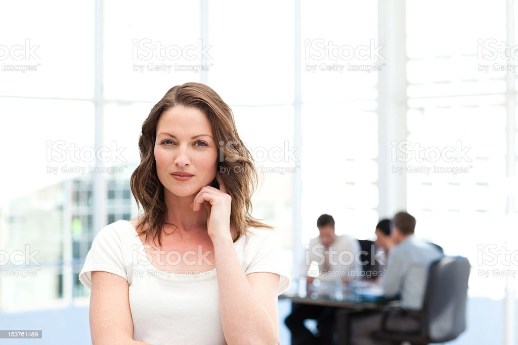 Pensive businesswoman standing in front of her team while working stock photo