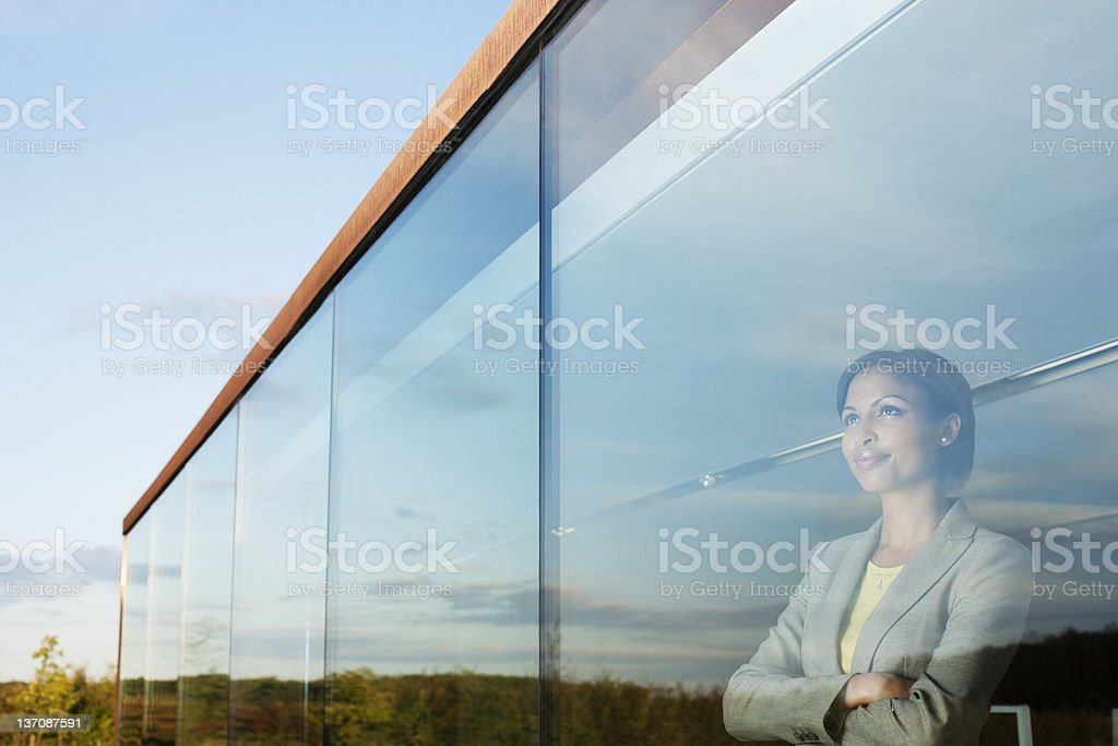 Pensive businesswoman with arms crossed in office window stock photo