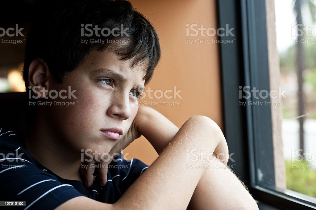 Pensive child looking through a window stock photo