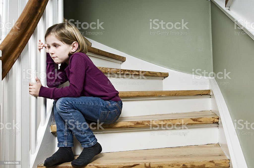 Pensive Child Watching Her Parents Argue. stock photo