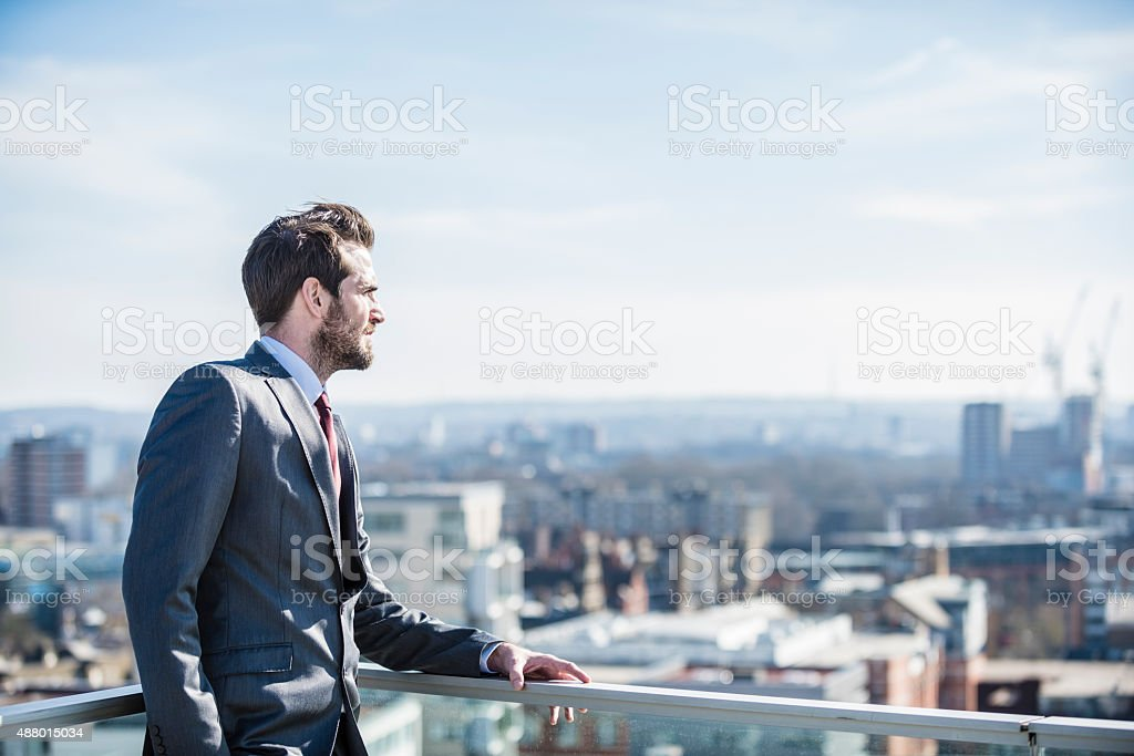 Pensive city businessman looking to horizon stock photo