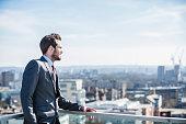 Pensive city businessman looking to horizon