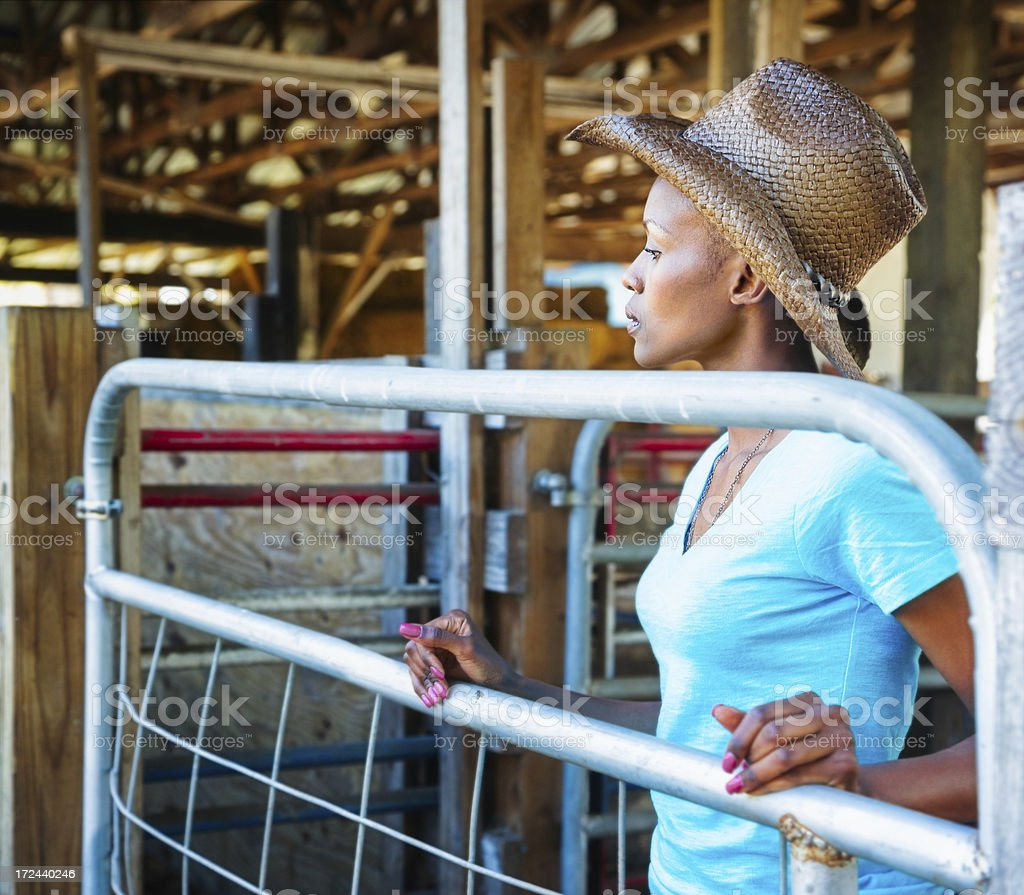Pensive cowgirl against metal pen gate royalty-free stock photo
