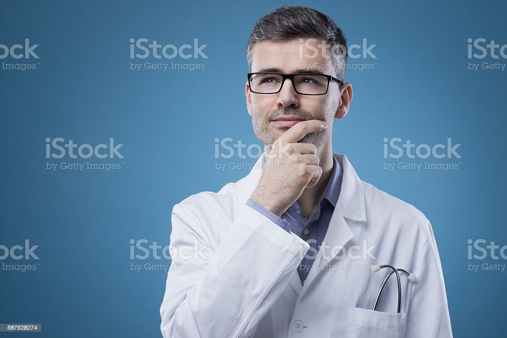 Pensive doctor with hand on chin stock photo