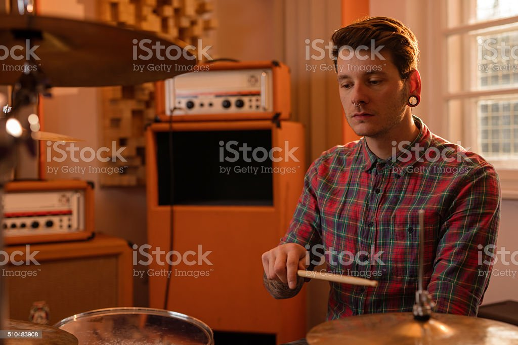 Pensive drummer in recording studio playing drums. stock photo