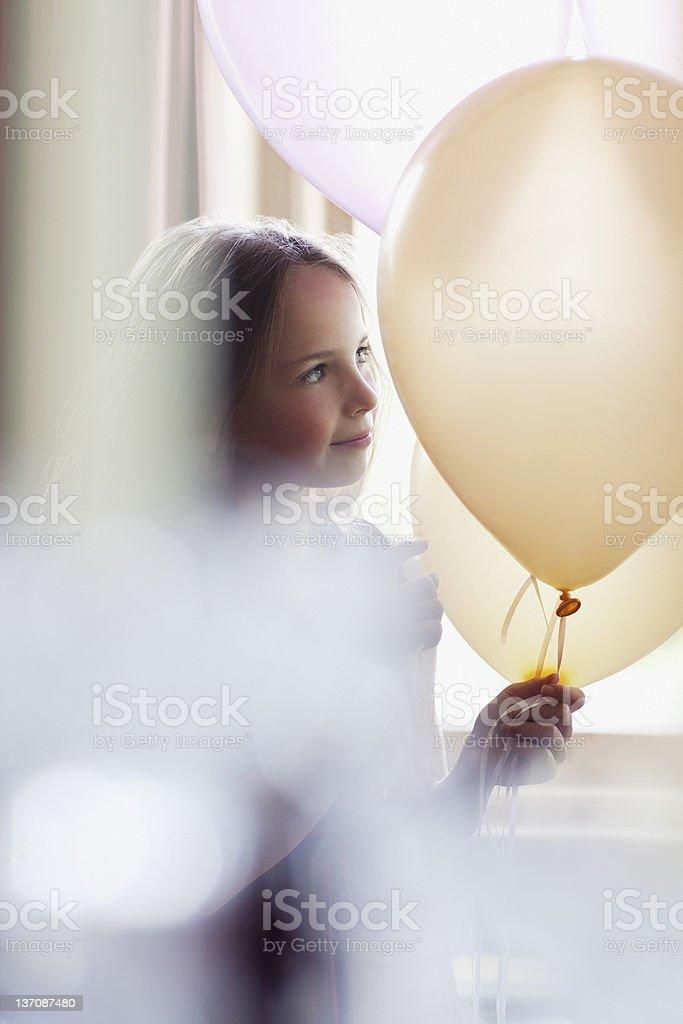 Pensive girl holding white balloons royalty-free stock photo