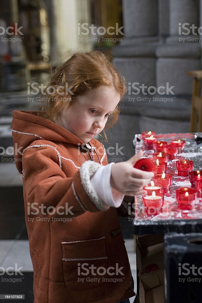 Pensive girl in church, lighting a candle royalty-free stock photo