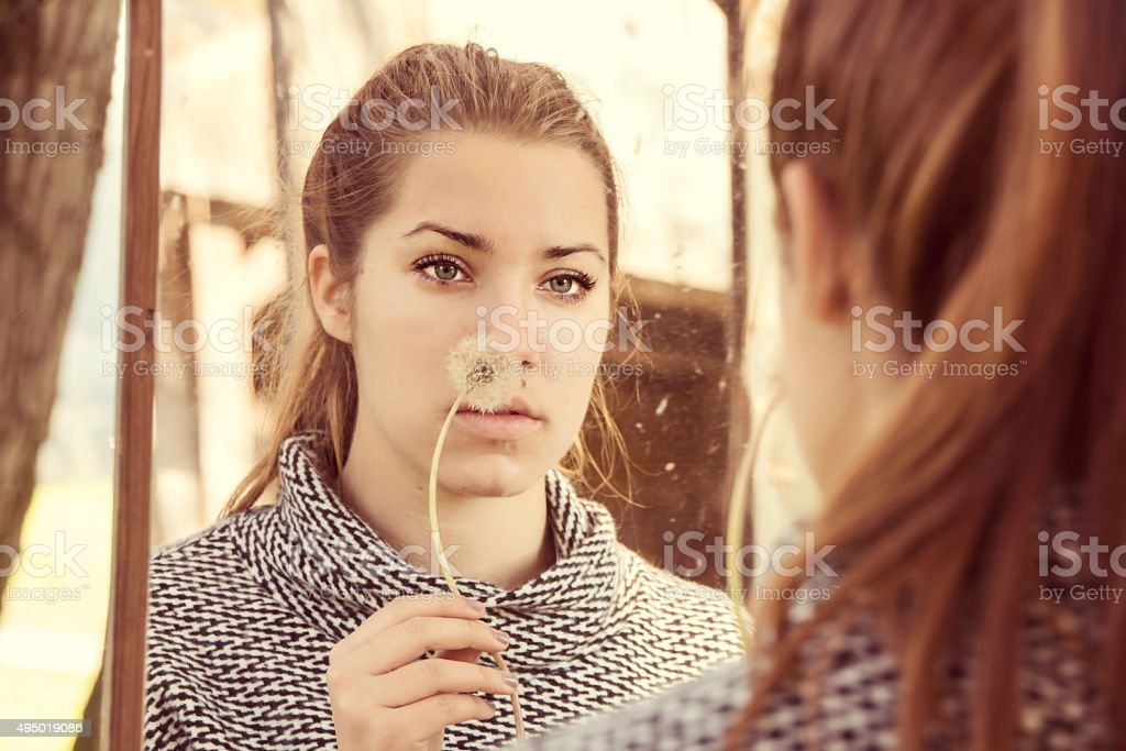 Pensive girl looking in mirror stock photo