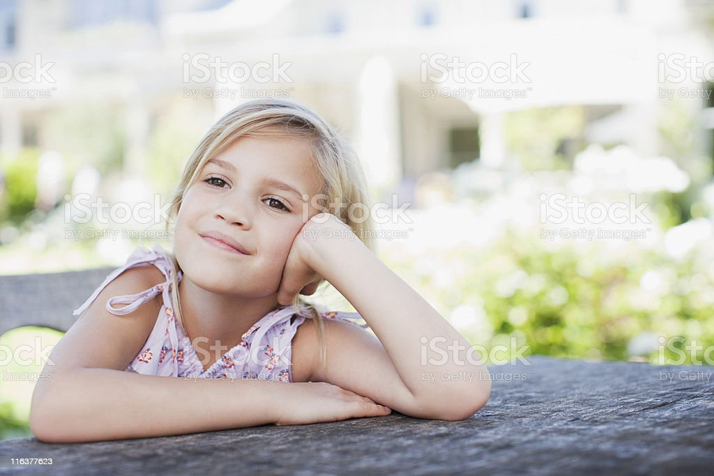 Pensive girl sitting at table outdoors stock photo