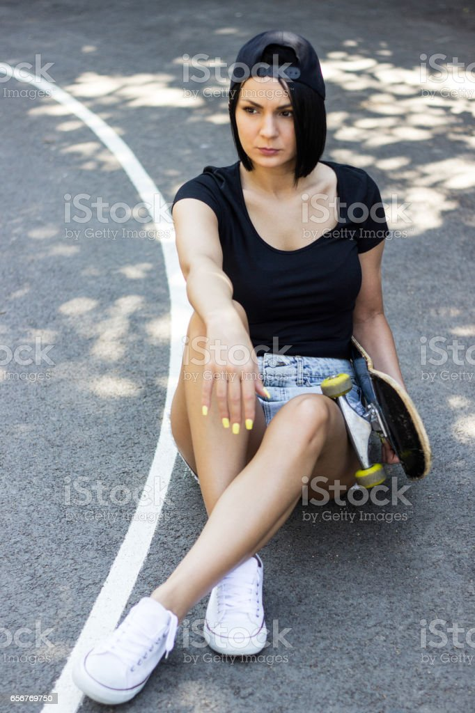 Pensive girl with her skateboard stock photo