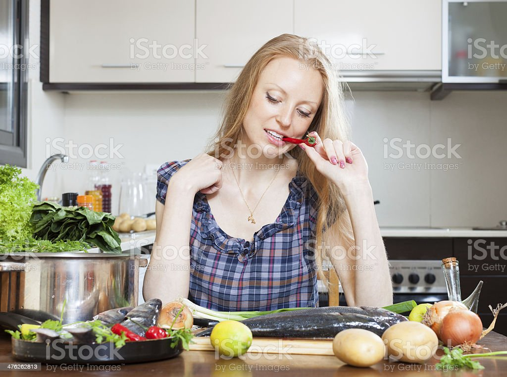 pensive housewife is thinking how to cook  fish royalty-free stock photo