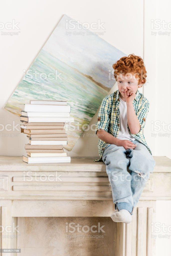 pensive little boy sitting on fireplace near pile of books stock photo