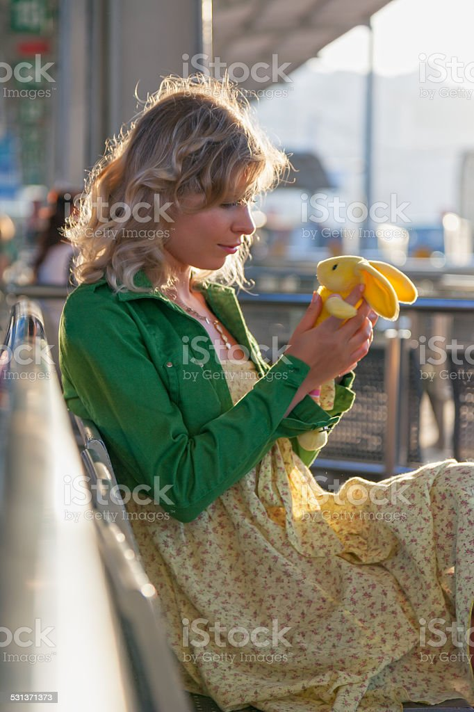 Pensive lonely woman sits at bus station holding a toy stock photo