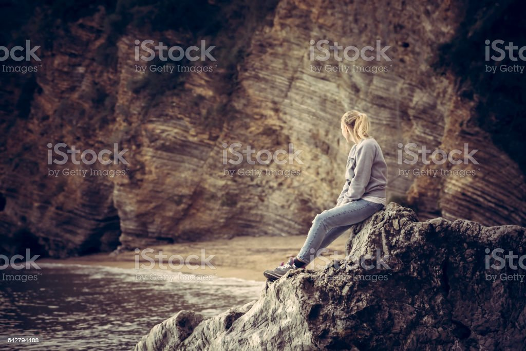 Pensive lonely young woman traveler relaxing on a big cliff stone on the beach looking at wild mountain scenery in retro vintage style stock photo
