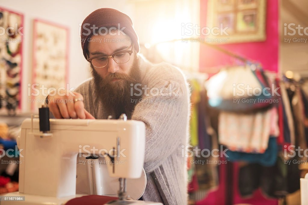 Pensive male tailor relaxing in a clothing design studio. stock photo