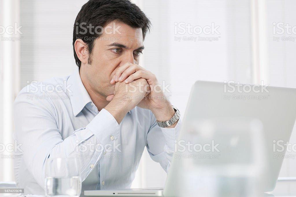 Pensive man at laptop stock photo