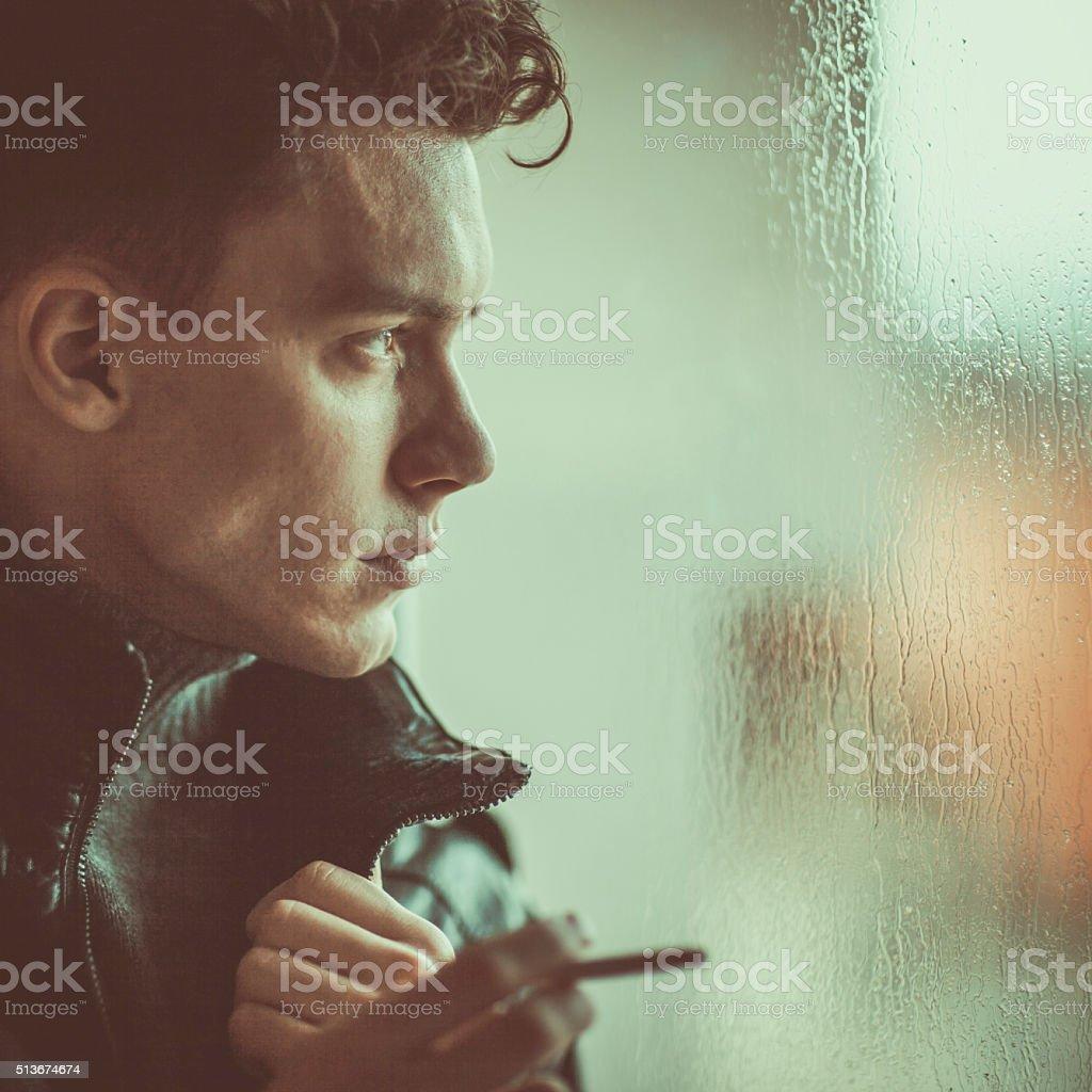 Pensive man looking through window on rainy day stock photo
