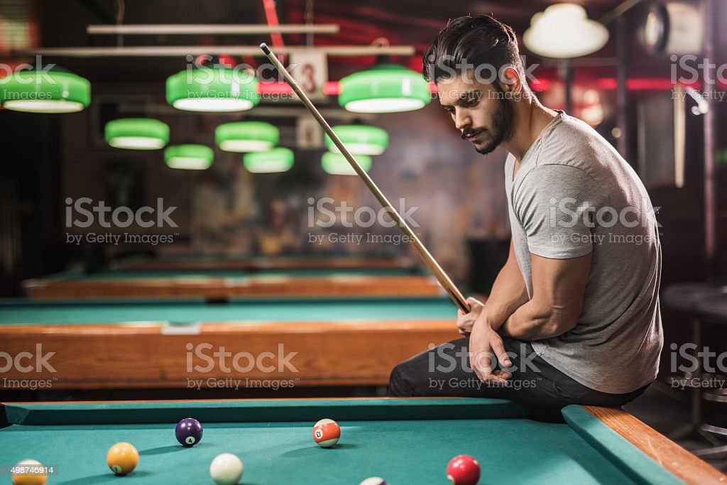 Young pensive man thinking of his next move in a pool hall.