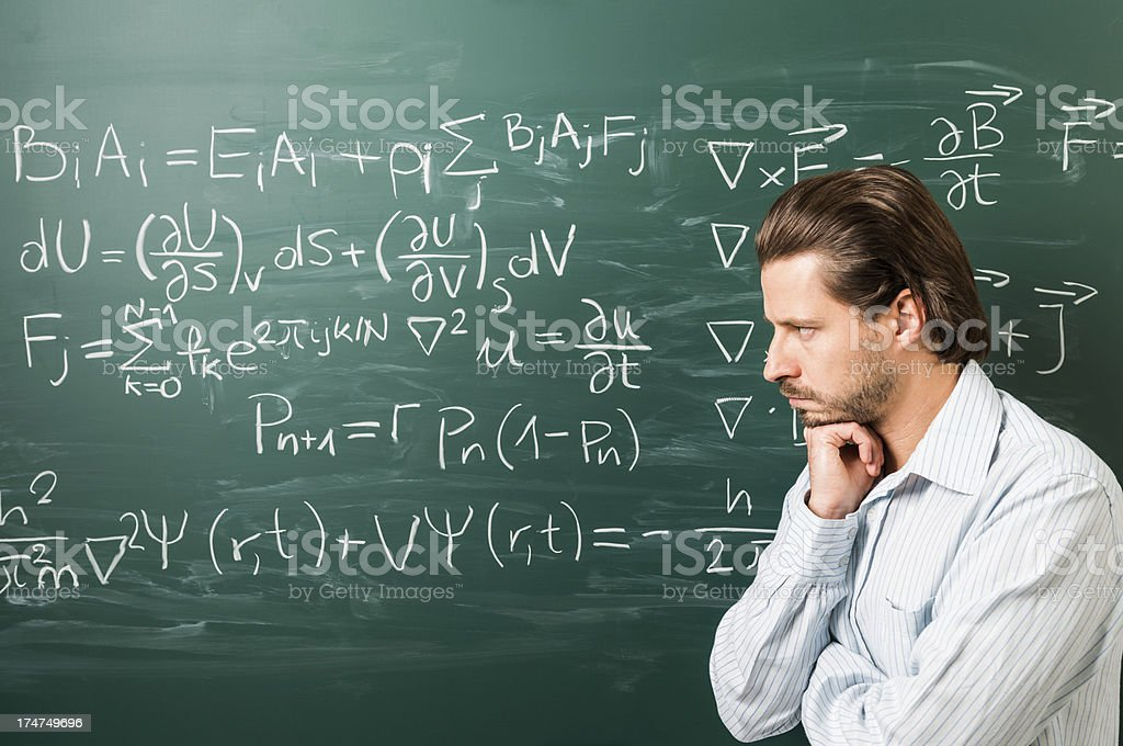 Pensive man standing against mathematical formula on green chalkboard royalty-free stock photo
