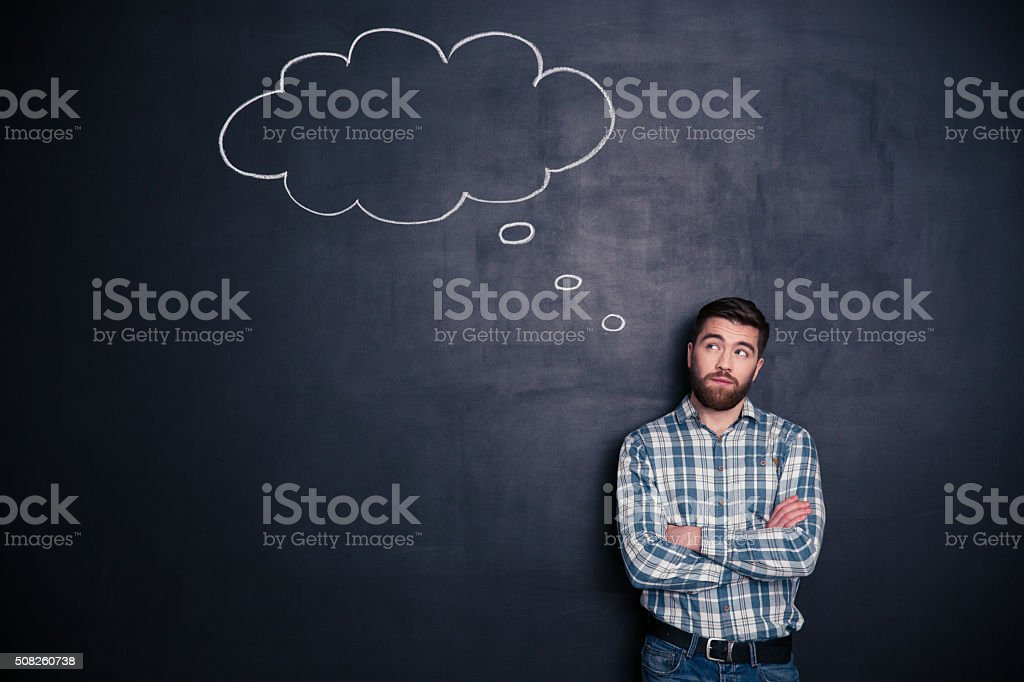 Pensive man standing with arms folded stock photo