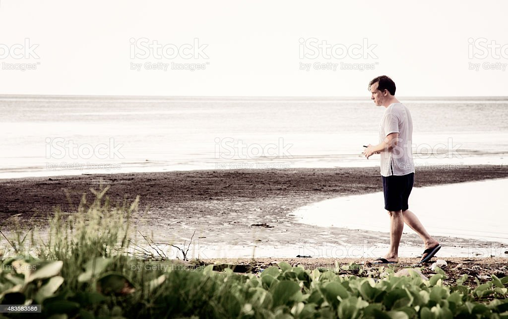Pensive man walks on polluted beach with sad expression stock photo