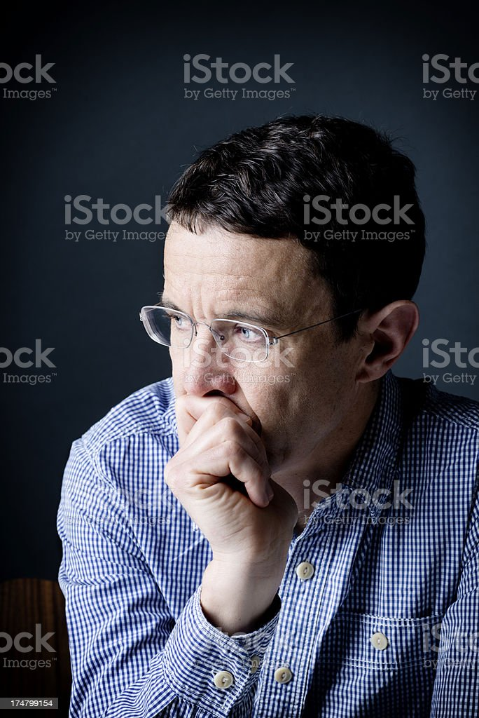 Pensive man wearing glasses lost in thought royalty-free stock photo