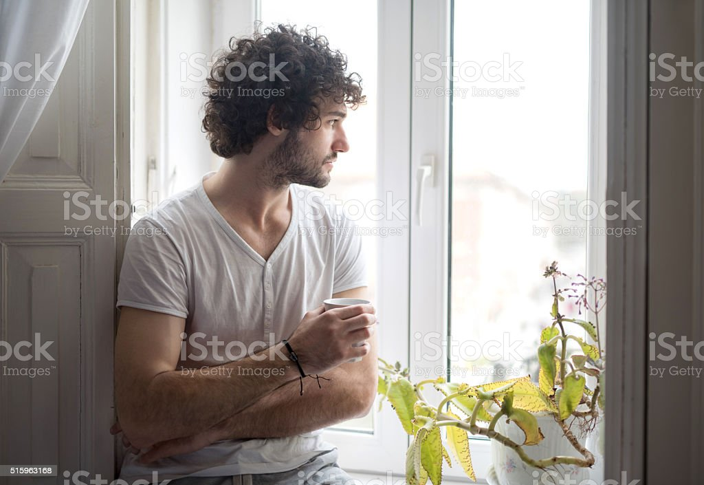 Pensive man with coffee cup looking through the window. stock photo
