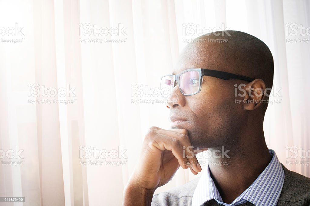 Pensive mature bald black man by a window stock photo