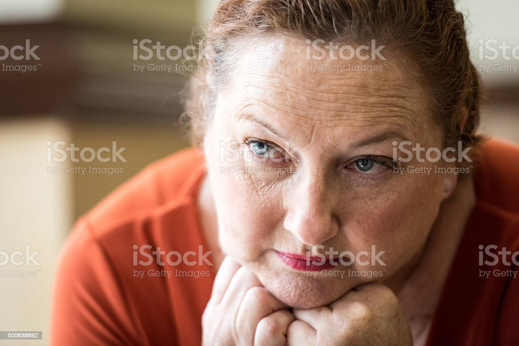 Pensive mature woman looking away stock photo