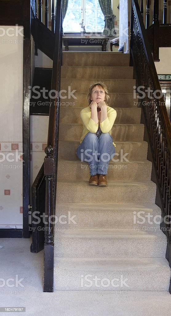 Pensive mature woman on the staircase royalty-free stock photo