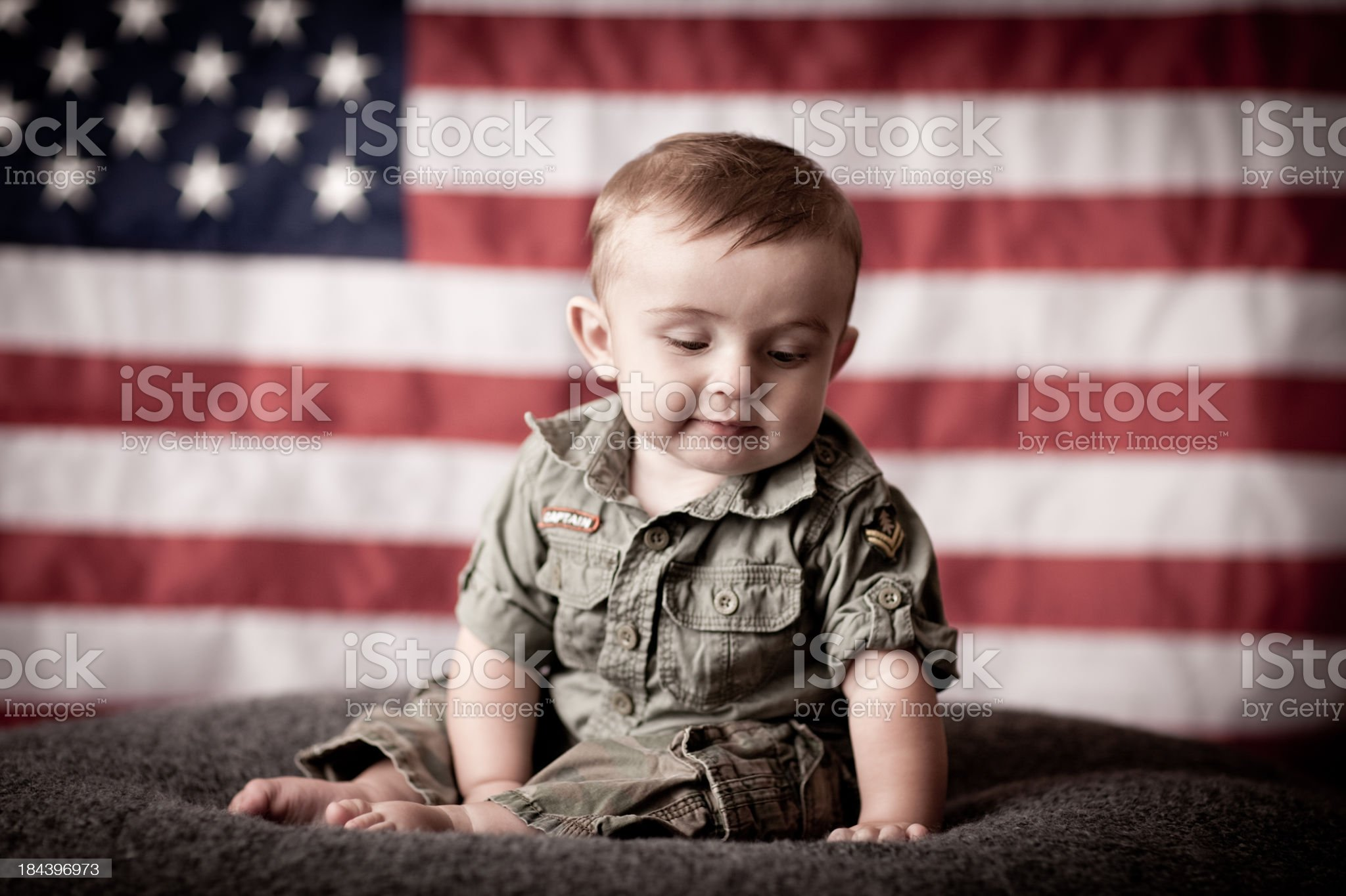 Pensive Military Baby Child Sitting by American Flag While Thinking royalty-free stock photo