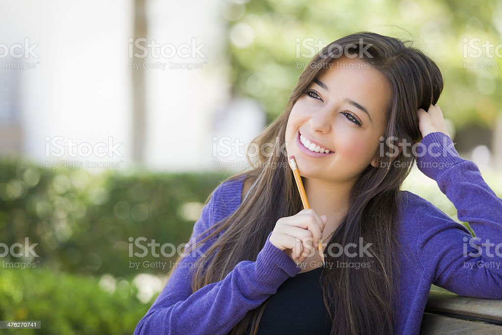 Pensive Mixed Race Female Student with Pencil on Campus stock photo