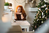 Pensive redhead woman spending a Christmas day at home.