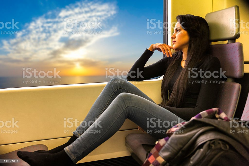 Pensive relaxed young woman traveling on a train at sunset stock photo