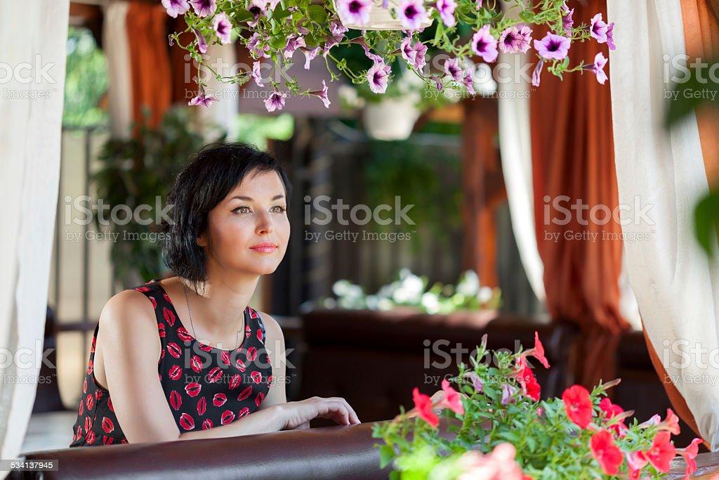 Pensive romantic woman sitting at terrace stock photo