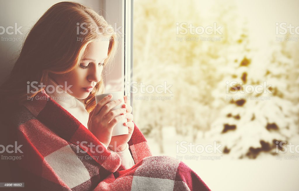 Pensive sad girl with a warming drink looking ou window stock photo