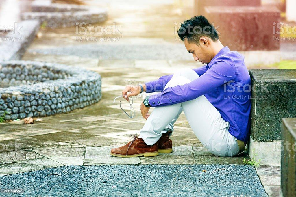 Pensive sad young Indonesian man sitting profile stock photo