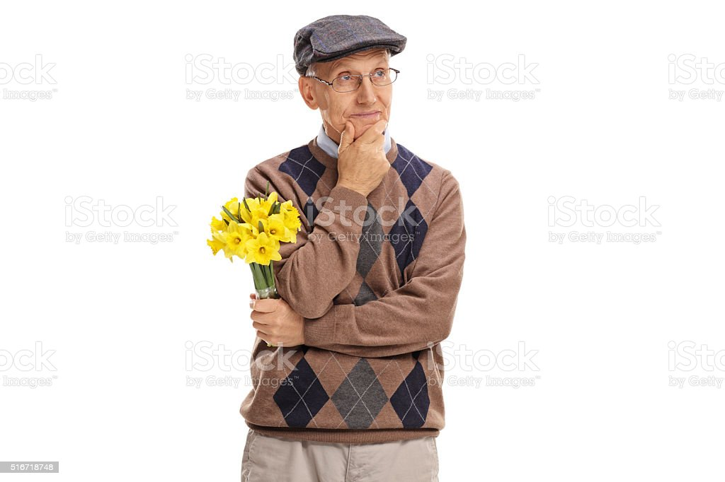 Pensive senior holding a bunch of flowers stock photo