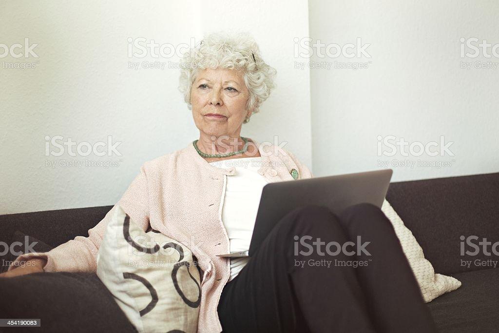 Pensive Senior Woman with Laptop stock photo