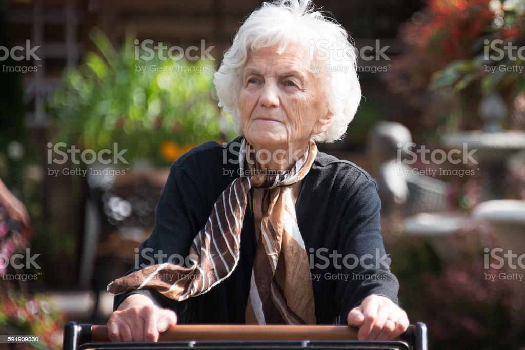 Pensive Senior Woman with Walker stock photo
