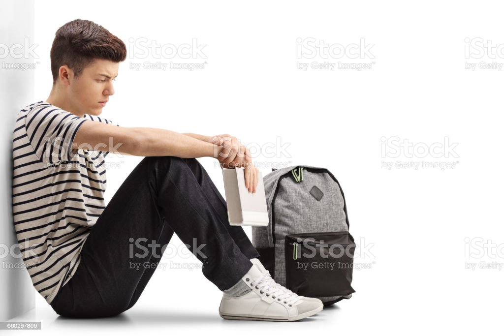 Pensive teen student leaning against a wall stock photo