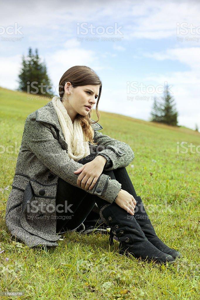 pensive teenage girl sitting on mountain royalty-free stock photo
